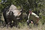 Art Wolfe, photographer kneeling next to a white rhinoceros in Kenya.