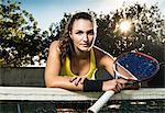 Female tennis player holding racket leaning on net