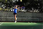 Female tennis player hitting ball