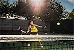 Female tennis player hitting ball over net