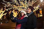 Young couple enjoying christmas celebrations on street