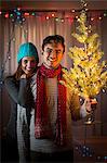 Young couple holding up illuminated christmas tree