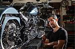 Portrait of mid adult man in motorcycle repair workshop