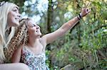 Two teenage girls exploring in woodland