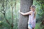 Teenage girl hugging tree in woodland