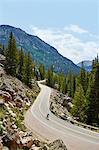 Cyclist on winding highway, Aspen, Colorado, USA