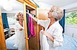 Senior woman selecting dress from closet at home