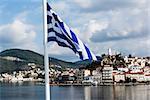 Greece, island of Poros behind a Greek Flag