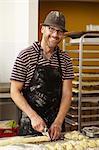 Male baker slicing dough in bakery