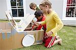 Boys pretending to mend a cardboard car