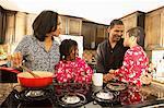 Mid adult couple and children preparing breakfast