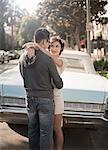 Couple embracing next to convertible car