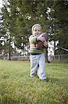 Toddler plays football in backyard