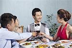 Friends congratulate a man while having dinner