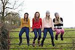 Four teenage girls sitting on gate