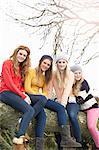 Four teenage girls sitting on tree trunk