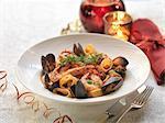 Calamarata seafood pasta with fresh mussels, king prawns, calamari, garlic, chillies, basil leaves, dill, white wine and tomato sauce among festive decorations