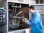 Worker shot blasting springs in laboratory