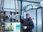 Engineer with industrial gearbox in engineering factory, portrait