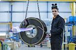 Portrait of engineer heat treating industrial gear in factory