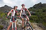 Young couple on mountain bikes taking a break