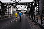 Two men running over city bridge