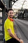 Portrait of young male runner taking a break on bridge
