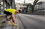 Young male runner tying shoelace on bridge