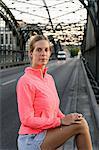 Portrait of young female runner on bridge