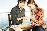 Man putting engagement ring on woman