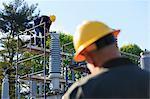 Power engineer performing maintenance on fluid filled high voltage insulator, Braintree, Massachusetts, USA