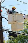 Power engineer in lift bucket working on power lines, Braintree, Massachusetts, USA