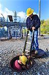 Power engineer entering manhole at a high voltage power distribution station, Braintree, Massachusetts, USA