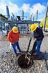 Power engineers looking inside manhole at high voltage power distribution station, Braintree, Massachusetts, USA