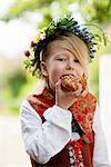 Girl in national costume eating cinnamon bun, Sandham, Sweden