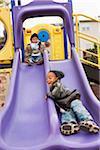 Brothers Playing on Playground Slide, Maryland, USA