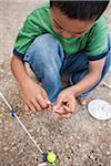Crouching Boy preparing Worm for Fishing, Lake Fairfax, Reston, Virginia, USA