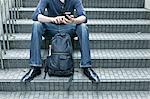 Man sitting on steps, using smartphone