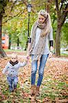 Mother and son walking across autumn leaves, Osijek, Croatia