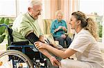 Nurse checks senior man's blood pressure in nursing home, Bavaria, Germany
