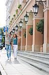 Tourist couple walking on sidewalk along building