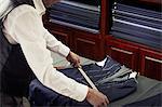 Tailor measuring garment in tailors shop