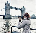 Female photographer taking photograph of Tower Bridge London, UK