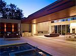 Dusk light over pool terrace open to the living room of Menlo Park Residence, USA.
