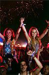 Cheering women on men's shoulders at music festival