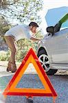 Man at roadside checking car engine behind warning triangle