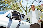 Portrait of confident senior man leaning against car