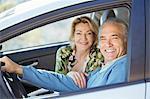 Portrait of happy senior couple in car