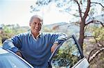 Portrait of happy senior man leaning on car