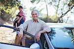 Portrait of senior man leaning on car